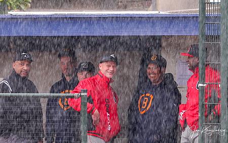 Coaches Reinier de Vries en Dè Flanegin in gesprek tijdens het oponthoud door de regen.